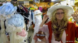 "Dee Dee trying on hats at a store in Tombstone, Arizona.  A sign next to the hats said, ""Hats are for buying, not for picture taking.""  Guess I musta missed it."