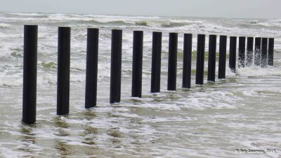 Barrier posts in surf, Padre Island National Seashore, Texas